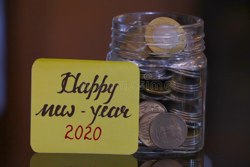 Happy New Year 2020. Money Jar. Happy New Year 2020 text on a paper, a clear glass jar filed with coins royalty free stock images