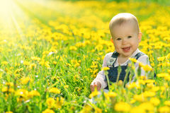 Happy baby girl on  meadow with yellow flowers  on the nature Stock Photo